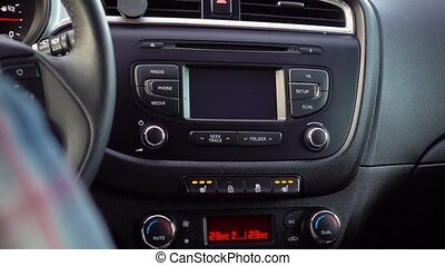 Hand presses a Heated Seat High button on a dashboard in a...