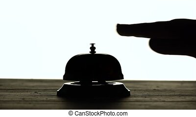 Hand presses the bell at the reception. White background....