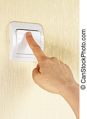 Hand presses the light switch on wall
