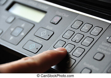 Hand pressing button on copy machine