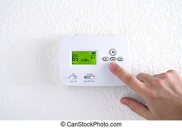 Hand pressing button on thermostat