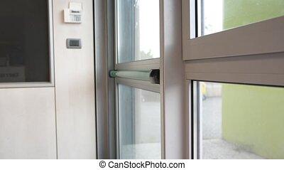 Hand pressing panic push bar to open door in case of...