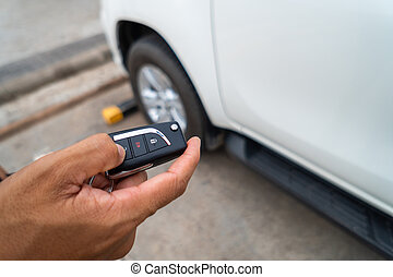 Hand pressing the button on the remote to lock or unlock the car with the remote control.