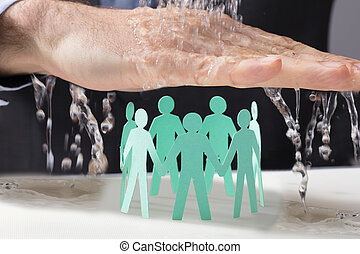 Hand Protecting Paper Cutout Human Figures From Water