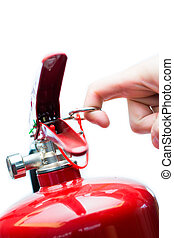 Hand pulling safety pin from fire extinguisher