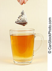 Hand pulls the tea bag from cup of tea