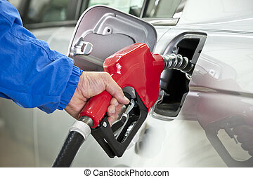 Hand Pumping Gas From Red Nozzle