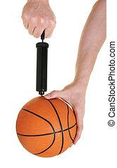 pumping up basketball - hand pumping up basketball over...