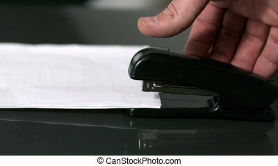 Hand pushing down on stapler - Hand pushing down on stapler...