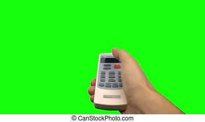 Hand pushing temperature button on air conditioner remote control. Green screen