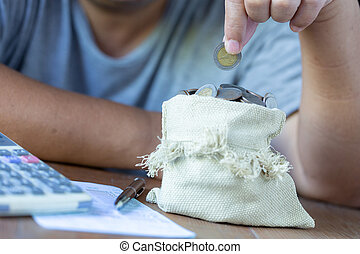 Hand put down money coin to bag on desk