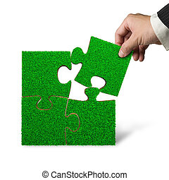 Hand put last piece of grass puzzle to complete