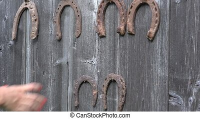 Hand put retro rusty horseshoes on old wooden rural house...