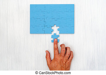 Hand put the last piece of puzzle