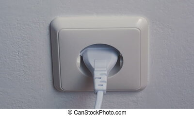 Hand puts a power plug in the wall socket - Close up of male...