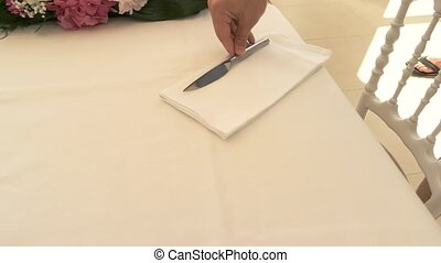 Hand puts knives on napkins. Tablecloth of white color....