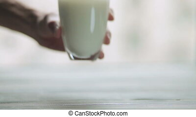 hand puts on the wooden table a glass of milk