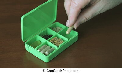 Hand puts pills in a container for tablets - Female hand...