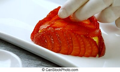 Hand puts slices of strawberry. Dessert with fresh berry....