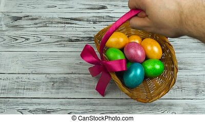 Hand puts the Easter basket with dyed and painted eggs on the table, concept of Christian feast Resurrection Sunday or Pascha