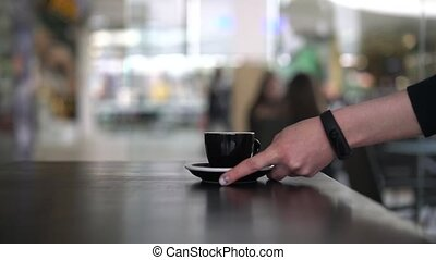 Hand putting a black cup on the table