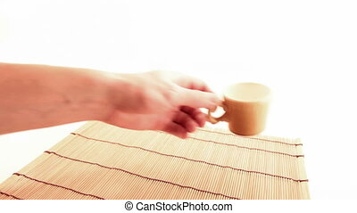 hand putting a cup on white