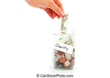 hand putting a dollar into a jar - charity donation