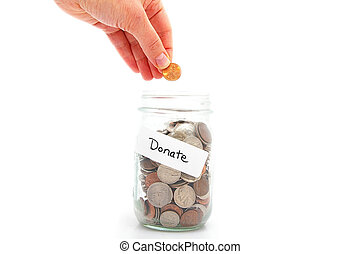 hand putting a penny in a money jar - charity donation