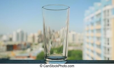 hand putting a pill into the a glass of water in slowmotion on blurred city background