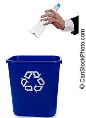 Hand putting an empty water bottle in a blue recycle bin