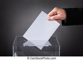 Hand Putting Ballot In Box - Close-up Of Hand Putting Ballot...