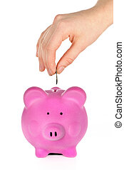 Hand putting coin into pink piggy bank slot