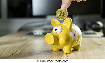 Hand putting golden bitcoin in to piggy bank money box with a computer on background. Cryptocurrency investment concept. BTC coin as symbol of electronic virtual money. Web banking, network payment.