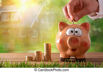 Hand putting money into piggy bank to buy a house