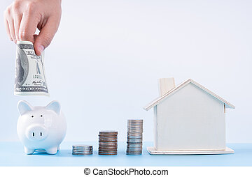 Hand putting money paper into piggy bank with wooden house and stack coins isolated grey background. Property investment and house mortgage financial concept.