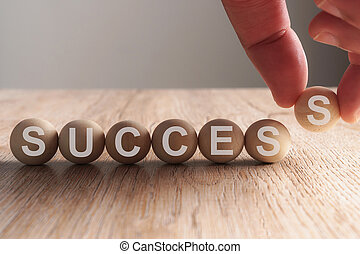 Hand putting on success word written in wooden ball