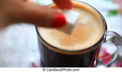 Hand putting sugar cube into a cup of coffee and stirring...