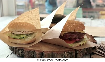 Hand puttings burger into package. Fast food on wooden...