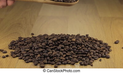 Hand quickly pours the coffee beans from a wooden spoon onto a pile of coffee beans.