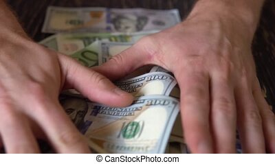hand rakes dollar bills on a wooden table, background of banknotes