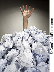 Hand reaches out from heap of papers