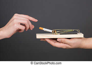Hand reaching cigarette from mousetrap