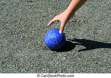 Hand reaching for a bocce ball