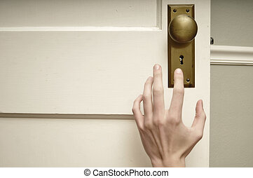 Hand reaching for doorknob - Pale hand reaching for golden...