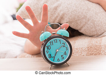 Hand reaching the alarm clock