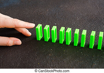 Hand ready to push domino piece to cause chain reaction. Row of green dominoes on dark background