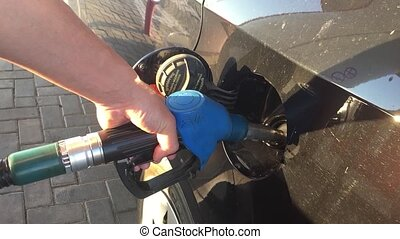 Hand refilling car with fuel. Refuel station. Car refueling on petrol station. Man oil pumping gasoline