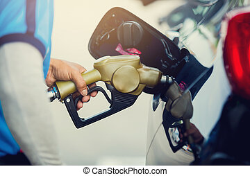 Hand refilling the car with fuel at the gas station.
