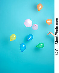 hand releasing colorful balloons on blue background
