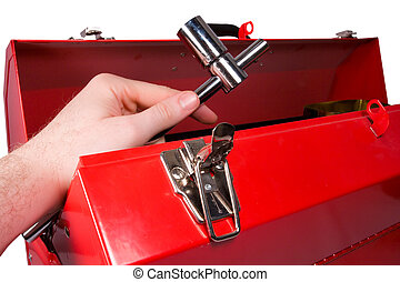 Hand removing a wrench from a toolbox - A hand removing a ...